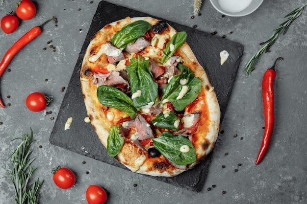 Pizza italiana di carne con roast beef, fette di bistecca, formaggio fuso, con fette di oliva e formaggio cheddar. primo piano, macro. concetto di tempo della pizza.