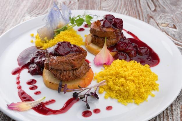 Medaglioni di carne con salsa su un piatto bianco