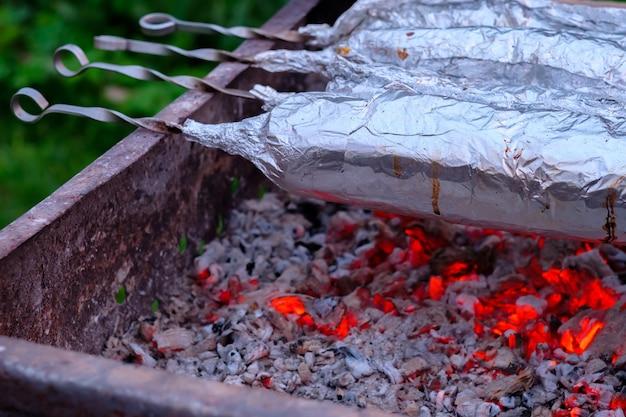 La carne su spiedini di metallo viene avvolta in un foglio di alluminio e grigliata su carbone di legna