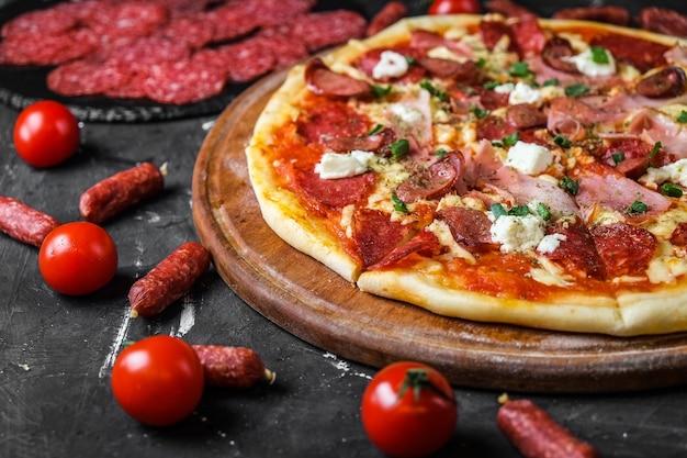 Pizza di carne con salame, prosciutto, pollo, salsicce e formaggio feta, su una lavagna e su una superficie scura
