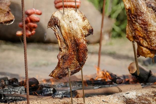 Carne arrosto e tagliata sul tavolo e fuoco di bivacco con legna da ardere in stile gaucho