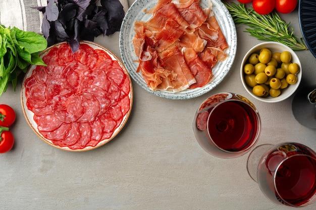Affettare e vino della salsiccia della carne su gray