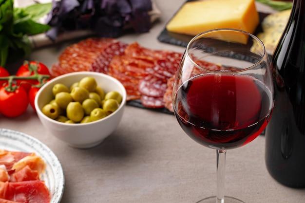 Affettare e vino della carne su fondo grigio