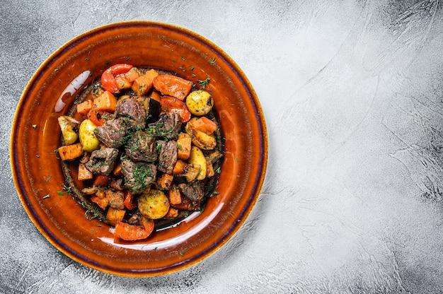 Spezzatino di carne, gulasch su un piatto. sfondo bianco. vista dall'alto. copia spazio.