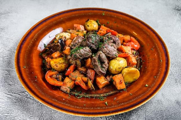 Spezzatino di carne, gulasch su un piatto. sfondo bianco. vista dall'alto.
