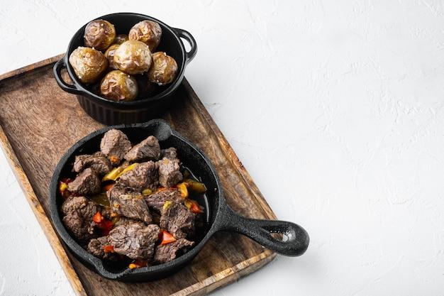 Spezzatino di carne con peperone dolce e set di foglie di alloro, in padella in ghisa, su superficie di pietra bianca, con spazio per la copia per il testo