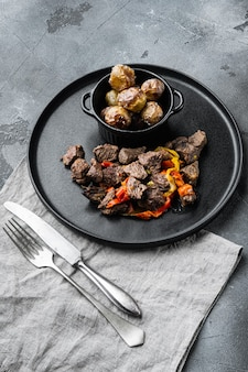 Spezzatino di carne con peperone dolce e alloro, su pietra grigia