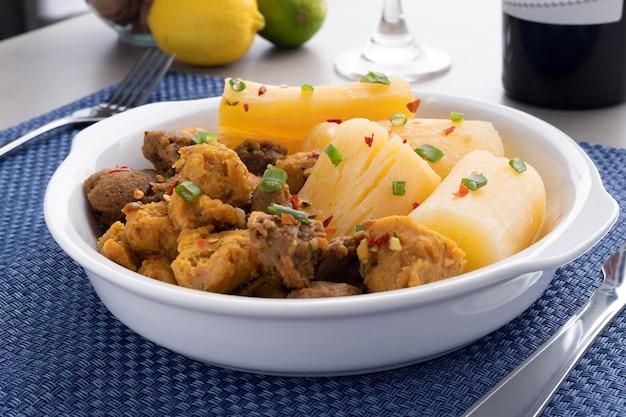 Carne con manioca su un piatto bianco con limone, vetro e vino in background.