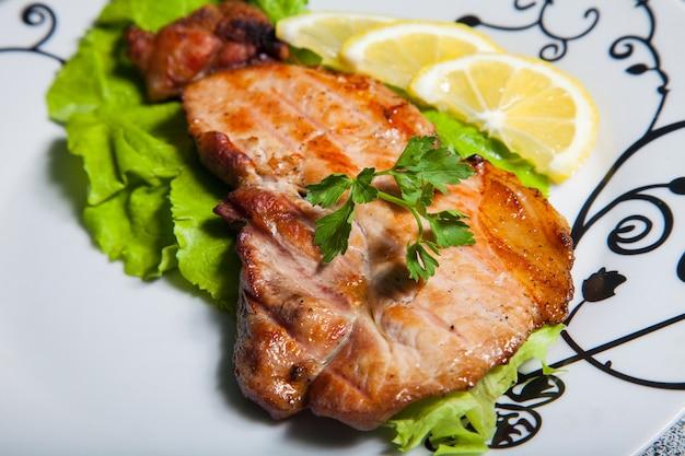 Carne con insalata e limone su un piatto bianco