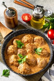 Polpette in panna acida e salsa di pomodoro in padella su tavola di pietra