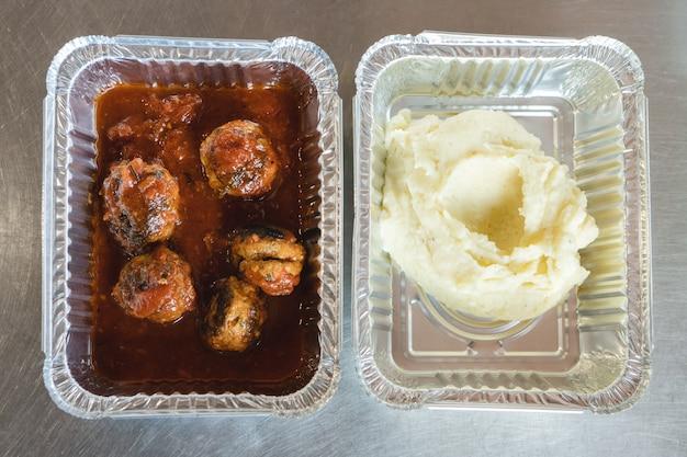 Polpette in salsa di pomodoro con purea in vassoi di alluminio. porta via. consegna