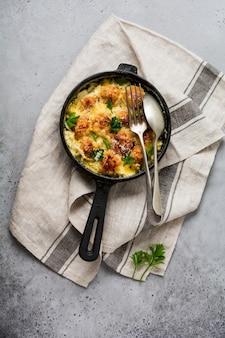 Polpette di carne con formaggio e salsa di panna in padella in ghisa su superficie grigia dell'annata