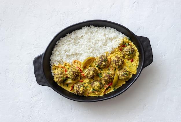 Polpette con riso, salsa al curry, lime e peperoncino. mangiare sano.