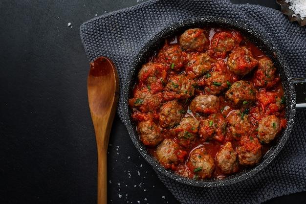 Polpette di carne con salsa di pomodoro servite in padella su sfondo scuro.