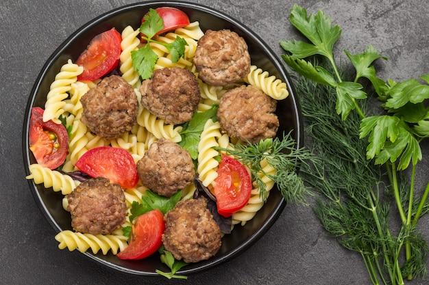 Polpette con pomodori e pasta in ciotola nera. aneto e rametti di prezzemolo. sfondo nero. lay piatto