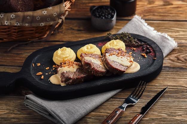 Polpettone con patatine fritte e verdure su una tavola di legno, cucina tradizionale inglese