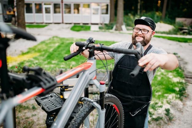Il meccanico regola il manubrio e i freni della bicicletta. ciclo officina all'aperto. lo sport in bicicletta, l'uomo di servizio barbuto lavora con la ruota