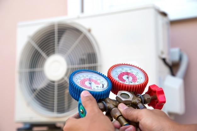 Riparazione dell'aria del meccanico tramite collettore per il riempimento del condizionatore d'aria domestico