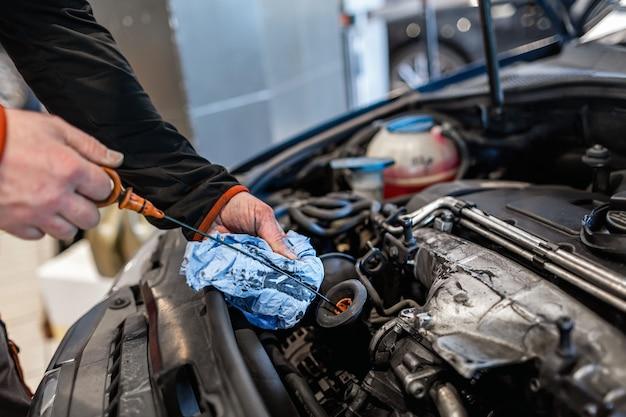 Meccanico in un'officina di riparazione auto che controlla l'olio in un veicolo
