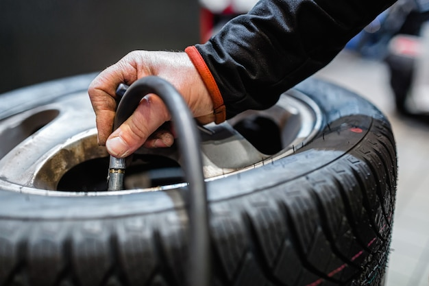 Meccanico in un'officina di riparazione auto il gonfiaggio di una ruota di veicoli