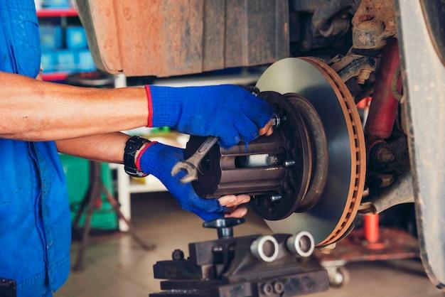 Garage auto di servizio auto meccanico nel centro mobile automobilistico. il meccanico dell'automobile passa le riparazioni dell'automobile