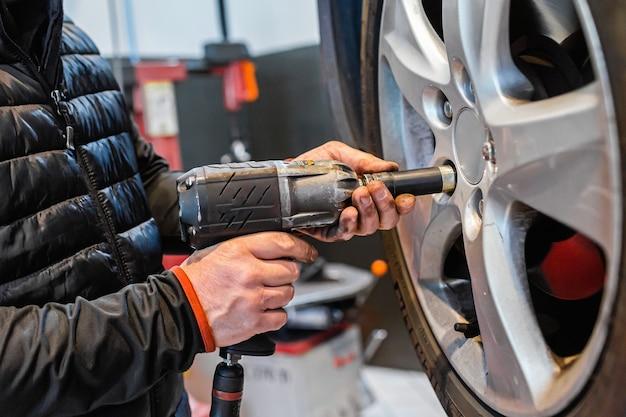 Meccanico in un'officina per auto allentando i dadi di una ruota del veicolo su un ascensore automatico