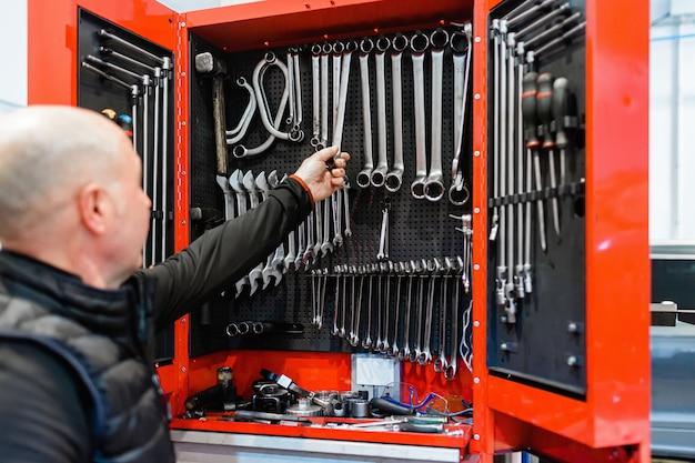 Meccanico in un'officina per auto prendendo strumenti di lavoro da un armadietto degli attrezzi
