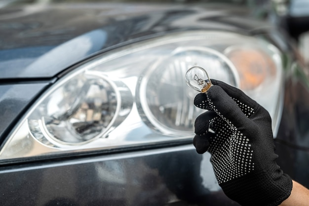 Il meccanico cambia la lampadina anabbagliante o abbagliante nella sua auto, primo piano