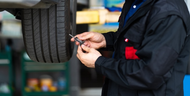 Controllo meccanico che controlla la profondità del battistrada del pneumatico dell'auto. manutenzione auto e concetto di garage di servizio auto.