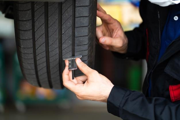 Controllo meccanico che controlla la profondità del battistrada dei pneumatici per auto. manutenzione auto e concetto di garage servizio auto.