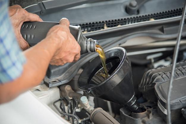 Meccanico che scarica olio motore da un'auto per un cambio d'olio in officina