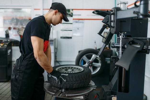 Meccanico che fissa la ruota rotta sulla macchina di montaggio del pneumatico, servizio di riparazione. l'uomo ripara pneumatici per auto in garage, ispezione automobilistica in officina