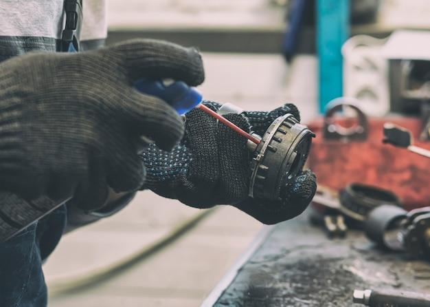Il meccanico che ripara una delle parti di auto funzionanti