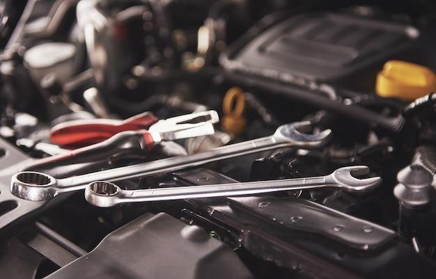 Mano del meccanico che controlla e che fissa un'auto rotta nel garage di servizio auto.