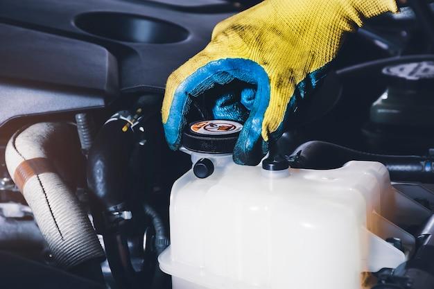 La mano del meccanico è aperta o chiusa il tappo del serbatoio del liquido di raffreddamento del radiatore dell'auto