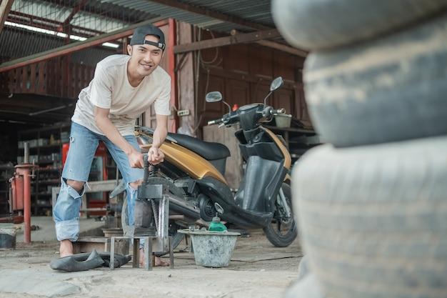 Meccanico che ripara a mano il pneumatico in officina