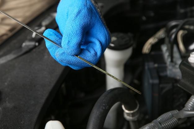 Il meccanico con le mani nei guanti controlla il livello dell'olio motore nell'auto