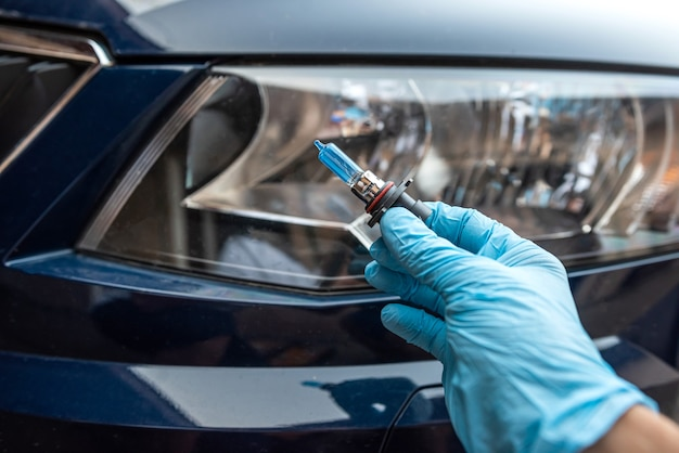 Il meccanico tiene la lampadina alogena dell'auto per la riparazione contro il faro dell'auto in background