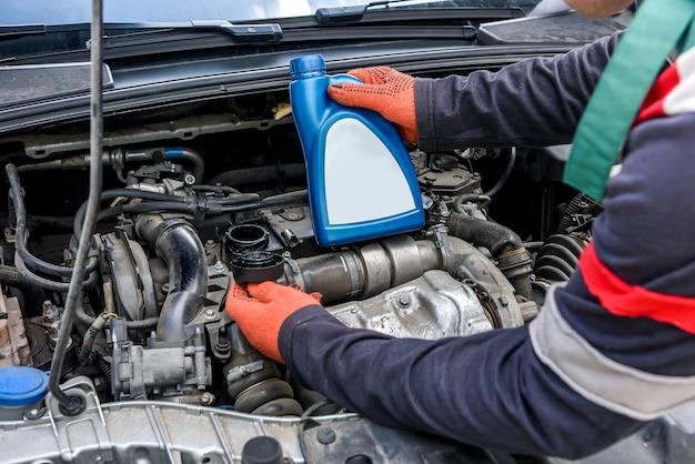 Il meccanico tiene le bottiglie con olio vicino al motore dell'auto car
