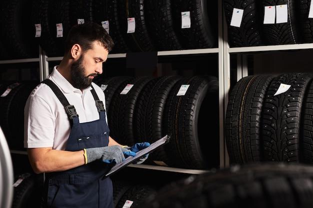 Meccanico che tiene il documento cartaceo tablet nelle mani mentre controlla l'assortimento nel servizio di riparazione auto, meccanico esperto che lavora solo nel garage di riparazione automobilistica, serve i clienti