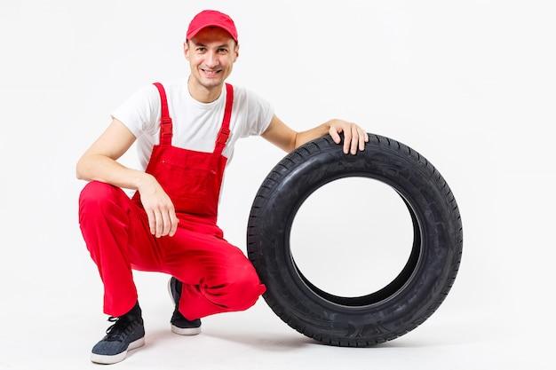 Meccanico che tiene una gomma al garage di riparazione. sostituzione di pneumatici invernali ed estivi.