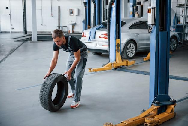 Meccanico in possesso di un pneumatico presso il garage di riparazione