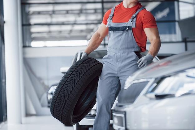 Meccanico che tiene una gomma al garage di riparazione. sostituzione di pneumatici invernali ed estivi