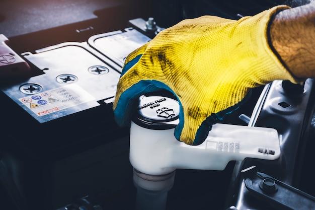 Il meccanico sta aprendo il tappo del serbatoio del liquido lavavetri per controllare il livello del liquido