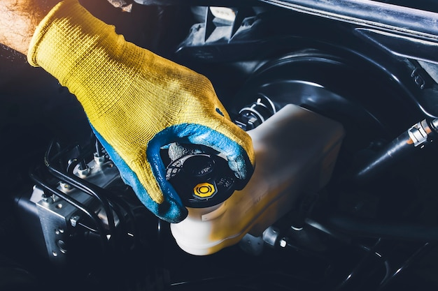 Il meccanico è aperto o chiude il tappo del serbatoio del liquido dei freni dell'auto per controllare il livello del liquido dei freni