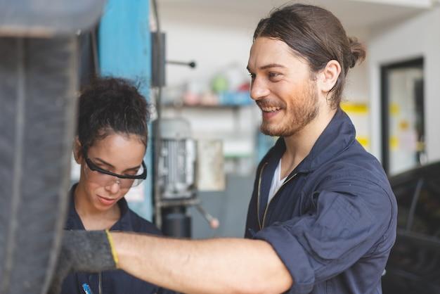 Meccanico maschio sorridente mentre si cambia pneumatico della macchina con il meccanico collega in garage di servizio auto