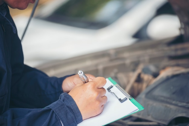 Mani dell'uomo meccanico che controllano pneumatici per auto all'aperto in loco servizio garage auto per centro automobilistico