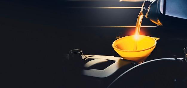Meccanico che versa olio lubrificante al motore dell'auto nel garage di riparazione con spazio per le copie