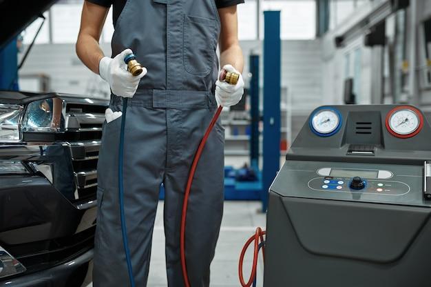 Uomo meccanico ricarica il condizionatore d'aria in officina meccanica
