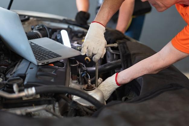 Meccanico che utilizza lo strumento chiave con il laptop che controlla e ripara la manutenzione del motore nel garage di servizio auto